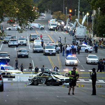 A damaged Capitol Hill police car is surrounded by crime scene tape on Constitution Avenue near the US Capitol (AP)