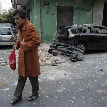 A woman walks in front of the damaged Panathinaikos fan club office in Athens (AP)