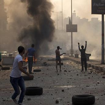 Supporters and opponents of Egypt's ousted Islamist president Mohammed Morsi clash in Cairo during a holiday marking the anniversary of the last war with Israel (AP)