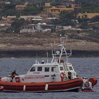 The Italian coast guard recover a migrant's body off Lampedusa (AP)