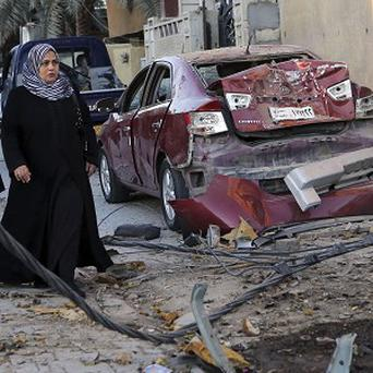 Women walk past the aftermath of a car bomb attack in Baghdad. (AP)