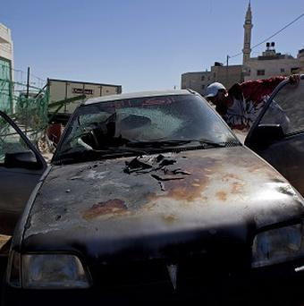 A Palestinian man inspects a burned vehicle in the village of Burka, on the West Bank. Residents says masked Jewish settlers torched three cars and defaced a mosque. (AP)