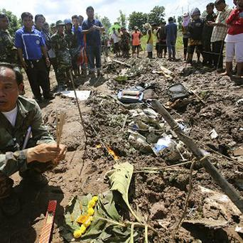 A Lao soldier prepares to place incense sticks into the ground beside the wreckage left by a Lao Airlines turboprop plane as he pays his respects to the victims fo the crash (AP)