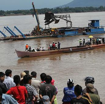 Onlookers watch the search operation for the crashed Lao Airlines plane on the banks of the Mekong River (AP)