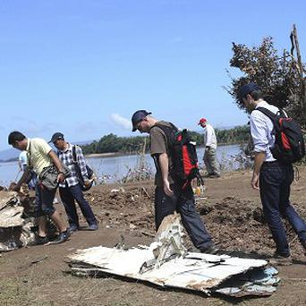 French investigators walk about bits of wreckage of a crashed plane in Pakse, Laos (AP)