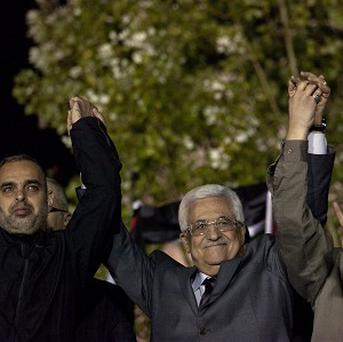 Palestinian president Mahmoud Abbas holds hands with freed prisoners during a welcome ceremony (AP)