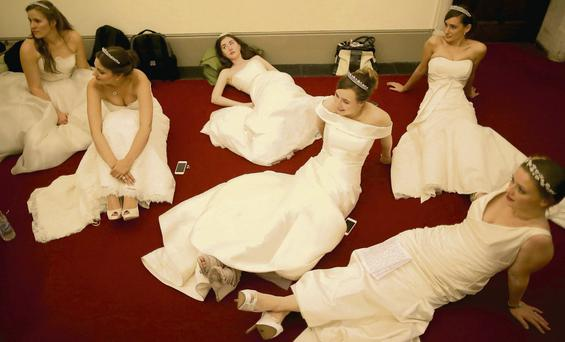 Debutantes rest their feet as they await the arrival of guests during the Queen Charlotte's Ball at the Royal Courts of Justice in London