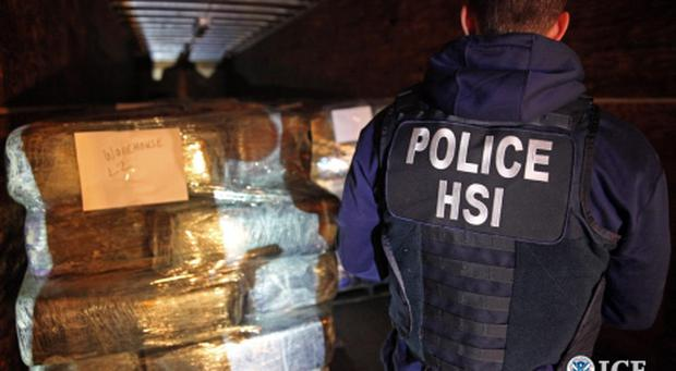 Photo provided by US Immigration and Customs Enforcement shows agents with bales of some of more than eight tons of marijuana and cocaine seized from a tunnel designed to smuggle drugs from Tijuana, Mexico, to San Diego.