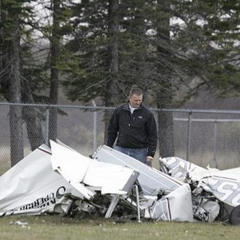 An investigator examines the wreckage of a plane that crashed in Wisconsin after a mid-air collision with another plane (AP/The News-Tribune, Steve Kuchera)