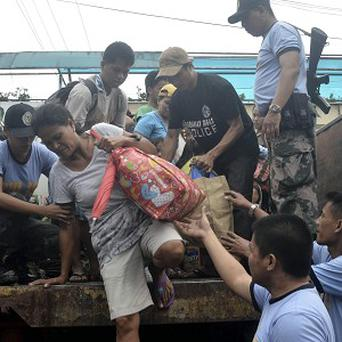 People living near the slopes of Mayon volcano are evacuated by police before Typhoon Haiyan roared in.