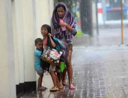A mother takes refuge with her children as Typhoon Haiyan hits Cebu city, central Philippines