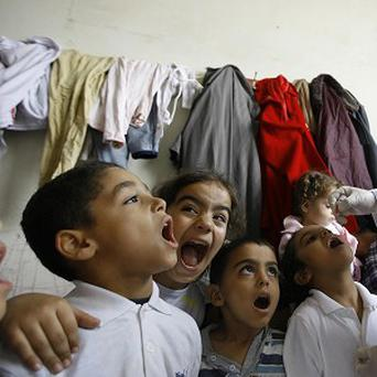 Displaced children line up to receive vaccination against polio at one of the Syrian refugee camps in the southern port city of Sidon, Lebanon (AP)