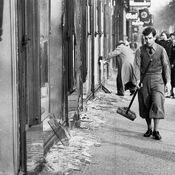 A youth with a broom prepares to clear up the broken window glass from a Jewish shop in Berlin.