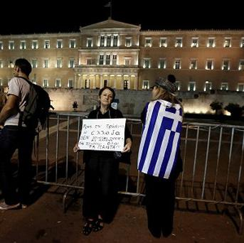 People gather outside Greece's parliament in support of an opposition motion of no confidence against the government.