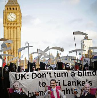 Amnesty supporters dressed as grim reapers, David Cameron, Sri Lankan president Mahinda Rajapaksa and Foreign Secretary William Hague protest at the UK government's endorsement of Sri Lanka at the Commonwealth Heads of Government Meeting in Colombo.