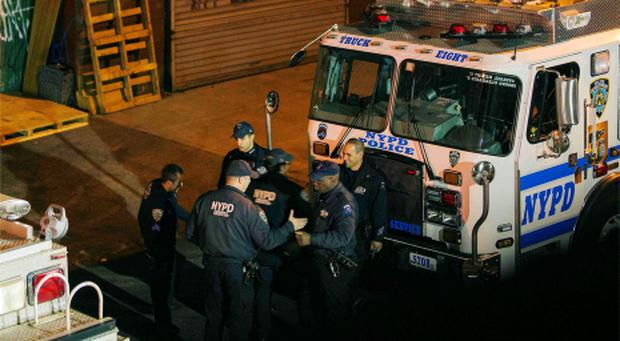 New York Police Department Officers depart a multiple shooting crime scene on Maujer Street in the Brooklyn borough of New York, November 11, 2013.
