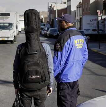 Police officers talks with a man carrying a guitar near a crime scene in the Brooklyn section of New York (AP)