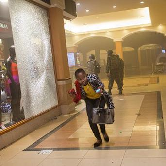 A woman runs for cover during September's mall attack in Kenya (AP)