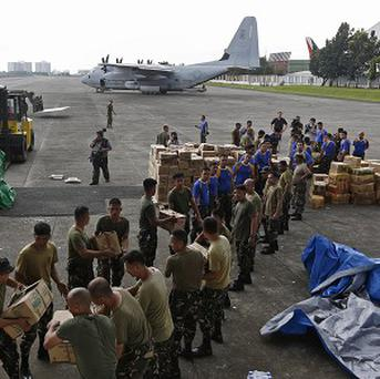 Eight people were crushed to death when thousands of typhoon survivors stormed a rice warehouse in the Philippines