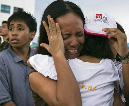 A woman with a child weeps as she queues for the chance to escape