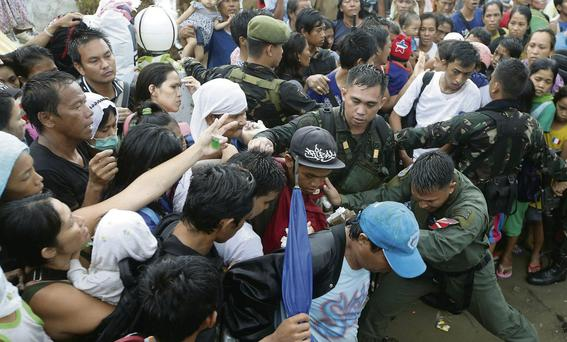 Survivors jostle to get on board a C-130 military transport plane in Tacloban yesterday, when thousands of survivors swarmed the airport seeking a flight out