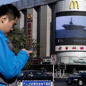 A Chinese man in Beijing checks his mobile phone as TV reports on the Philippines disaster (AP)
