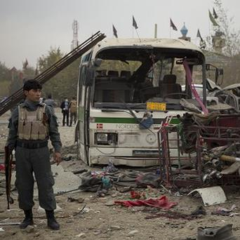 An Afghan policeman secures an area after a suicide vehicle bomb tore through the area on the outskirts of Kabul (AP)