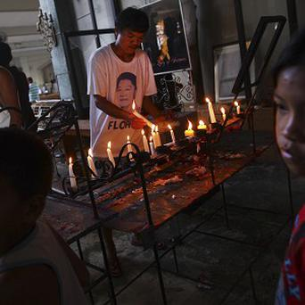 A man lights a candle as he attends a mass at Santo Nino church, which was damaged by Typhoon Haiyan, in Tacloban, Philippines (AP)