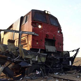 An Egyptian photographs the wreckage of vehicles struck by a train near the village of Dahshur, about 25 miles south of Cairo (AP)