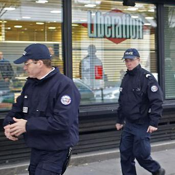 Police officers stand outside Liberation newspaper office in Paris after a gunman opened fire in the lobby (AP)