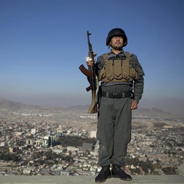 An Afghan policeman stands to attention at a checkpoint overlooking Kabul. (AP/Anja Niedringhaus)