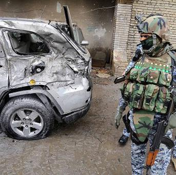 Security forces inspect the site of a car bomb attack in Baghdad's Karrada neighbourhood (AP)