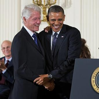 President Barack Obama greets former President Bill Clinton at the White House before awarding him the Presidential Medal of Freedom. (AP)