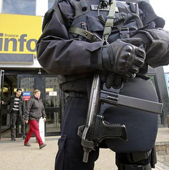A French police officer wearing a bullet-proof jacket stands at the entrance of France Info radio station in Paris