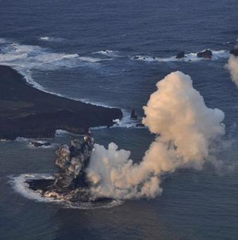 Smoke billows from a new island off the coast of Nishinoshima, seen left above, a small, uninhabited island in the Ogasawara chain, far south of Tokyo (AP/Japan Coast Guard)