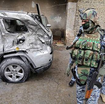 Security forces inspect the site of a car bomb attack in Baghdad on Wednesday (AP)