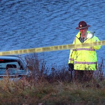 A police officer investigates the scene after a car went into a holding pond near a highway exit ramp in St Louis Park (AP/The Star Tribune, Elizabeth Flores)