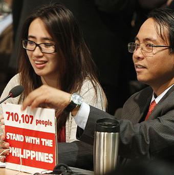 Philippine climate commissioner Naderev Sano, right, holds a sign during the closing session of the United Nations Framework Convention on Climate Change in Warsaw, Poland. (AP /Czarek Sokolowski)