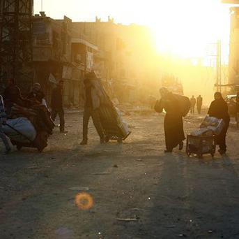 Syrian civilians flee from homes destroyed during clashes between government soldiers and opposition troops (AP)