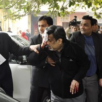 Rajesh Talwar, convicted of murdering his daughter, holds his face after being attacked outside court (AP)