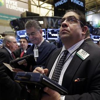 In this November 22, 2013, file photo, Robert Oswald, right, works with fellow traders on the floor of the New York Stock Exchange.