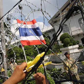 An anti-government protester puts a Thai national flag on barbed wire outside the interior ministry in Bangkok (AP)