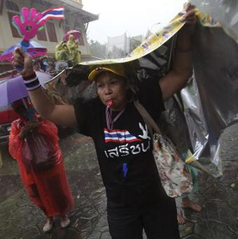 Braving the rain, anti-government protesters stage a rally outside Interior Ministry in Bangkok, Thailand (AP)