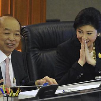 Thai Prime Minister Yingluck Shinawatra, right, with Foreign Minister Surapong Tovichakchaikul, after the no-confidence vote. (AP)