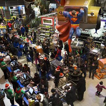 Customers wait to make their purchases at the Times Square Toys R Us store in New York (AP)