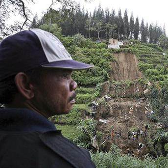 A man inspects the site where a landslide killed scores of people in Brastagi, North Sumatra, Indonesia (AP)