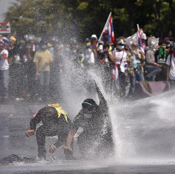 Anti-government protesters are sprayed by water in Bangkok, Thailand (AP)