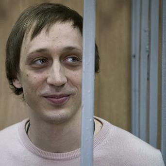 Pavel Dmitrichenko stands inside a barred enclosure at a courtroom in Moscow. (AP)