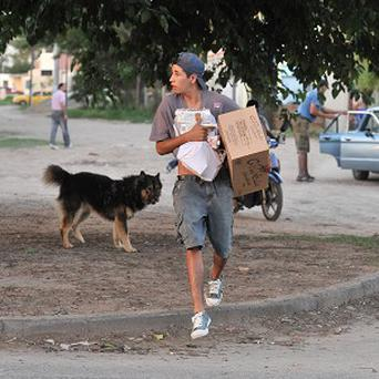 A man carries an armful of merchandise he took from a shop in Cordoba, Argentina (AP)