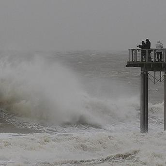 People look at the strong North Sea waves at a coastal town in Belgium (AP)